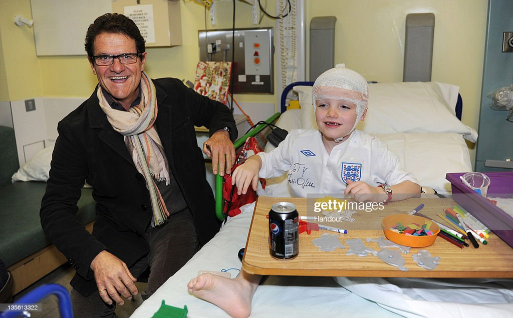 In this handout image provided by the FA, Manager <a gi-track='captionPersonalityLinkClicked' href=/galleries/search?phrase=Fabio+Capello&family=editorial&specificpeople=241290 ng-click='$event.stopPropagation()'>Fabio Capello</a> of England visits patient Tiarnan Smith on a visit to Great Ormond Street Hospital on December 12, 2011 in London, England.
