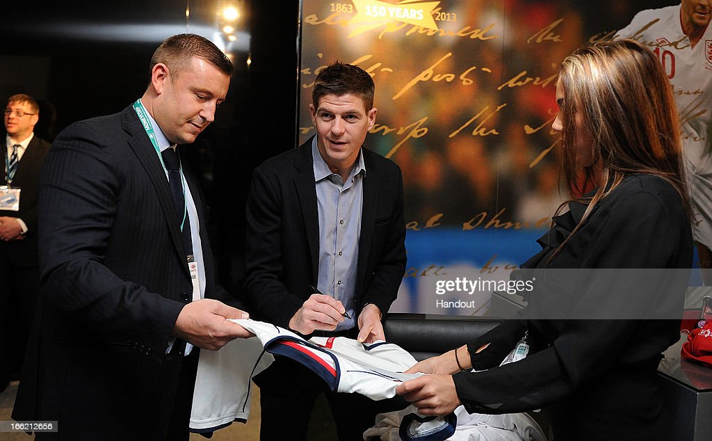 In this handout image provided by The FA, Steven Gerrard autographs a football shirt in the FA150 lounge during the Soccerex European Forum Conference Programme in Manchester on April 10, 2013 in Manchester England.