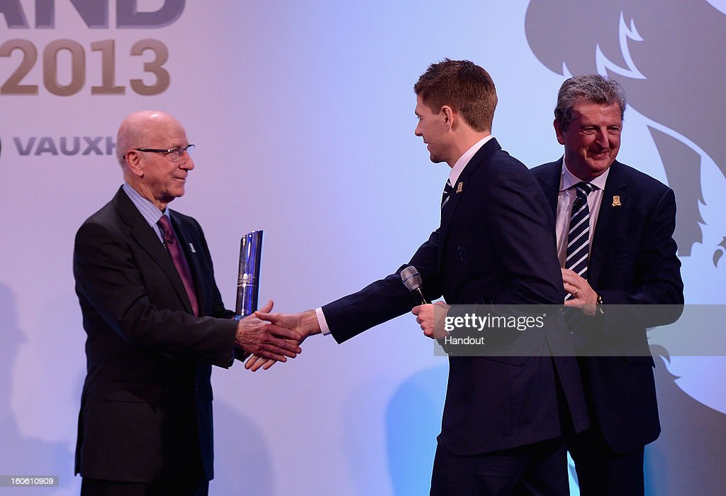 In this handout image provided by The FA, Steven Gerrard receives the Senior Men's Player of the Year award from Sir Bobby Charlton and England manager Roy Hodgson (R) during the FA England Awards 2013 at St. George's Park on February 3, 2013 in Burton-upon-Trent, England.