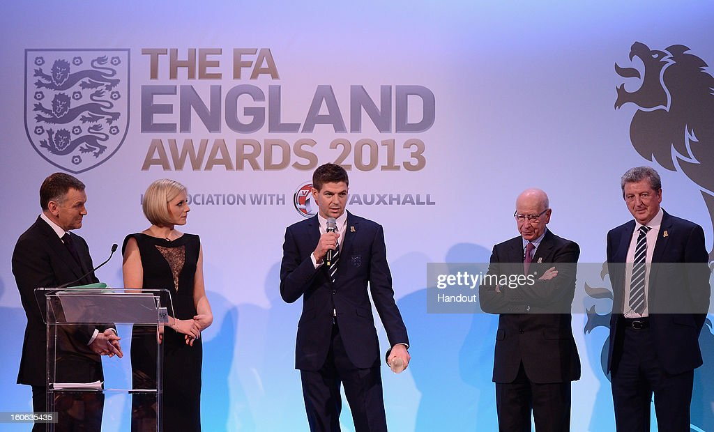 In this handout image provided by The FA, Steven Gerrard receives the Senior Men's Player of the Year award from Sir Bobby Charlton (2ndR) and England manager Roy Hodgson (R) during the FA England Awards 2013 at St. George's Park on February 3, 2013 in Burton-upon-Trent, England.