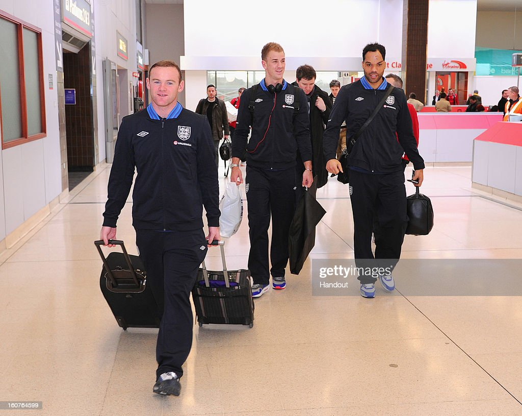 In this handout image provided by The FA, Wayne Rooney, Joe Hart and Joleon Lescott board a train as the England squad travel to London on February 5, 2013 in Birmingham England.
