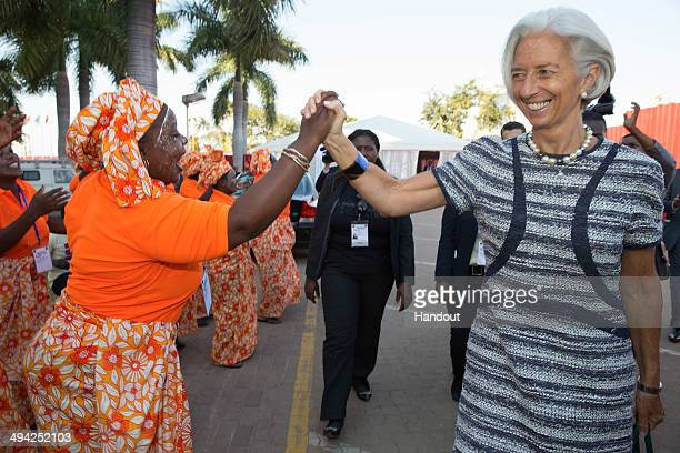 In this handout image provided by the International Monetary Fund IMF Managing Director Christine Lagarde is greeted by local singers as she attends...