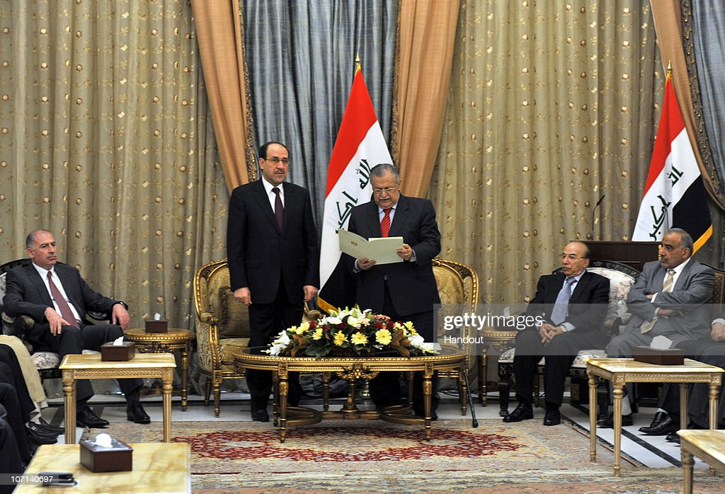 In this handout image provided by the Iraqi Presidents office, Iraqi President <a gi-track='captionPersonalityLinkClicked' href=/galleries/search?phrase=Jalal+Talabani&family=editorial&specificpeople=213582 ng-click='$event.stopPropagation()'>Jalal Talabani</a> (CentreR) hands Iraqi designate Prime Minister Nuri al-Maliki (CentreL) a formal request to form the next government, in the presence of other Iraqi political leaders, on November 25, 2010 at al-Salam Palace in Baghdad, Iraq. Al-Maliki has a 30-day period to choose his cabinet.