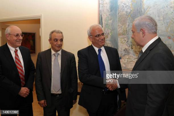 In this handout image provided by the Israeli Government Press Office Israel's Prime Minister Benjamin Netanyahu shakes hands with Palestinian chief...