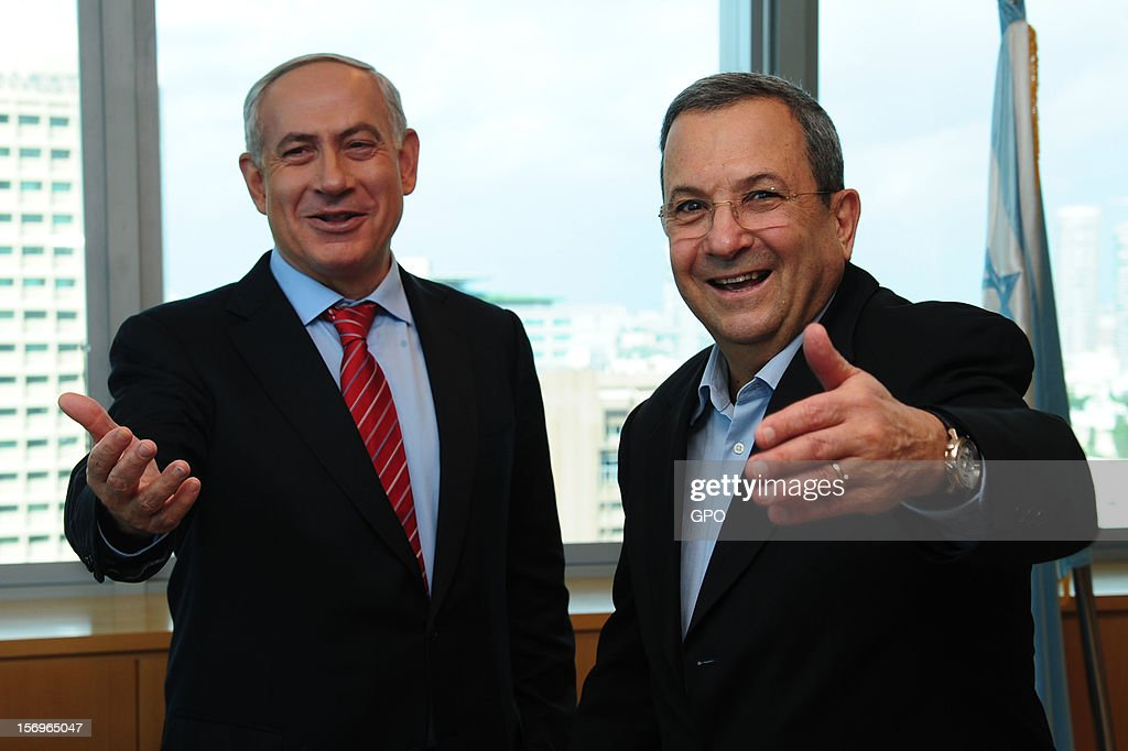 In this handout image provided by the Israeli Government Press Office (GPO), Prime Minister Benjamin Netanyahu (L) and Defence Minister Ehud Barak gesture and smile as Brig. Gen. Eyal Zamir (not pictured) is appointed the new military secretary, on November 26, 2012 in Tel Aviv, Israel. The appointment comes following eight days of conflict with Hamas.