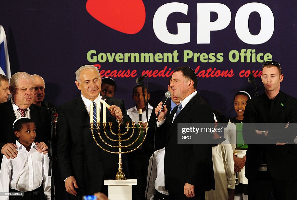 In this handout image provided by the Israeli Government Press Office (GPO), Prime Minister <a gi-track='captionPersonalityLinkClicked' href=/galleries/search?phrase=Benjamin+Netanyahu&family=editorial&specificpeople=118594 ng-click='$event.stopPropagation()'>Benjamin Netanyahu</a> lights candles on the Jewish holiday of Hanukkah during an event with members of the foreign press on December 10, 2012 in Jerusalem, Israel.