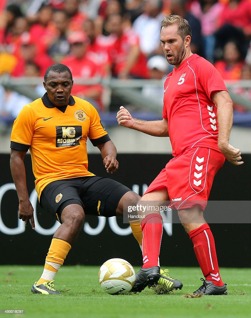 In this handout image provided by the ITM Group, Fanie Madida (L) and Jason McAteer during the Legends match between Liverpool FC Legends and Kaizer Chiefs Legends at Moses Mabhida Stadium on November 16, 2013 in Durban, South Africa.