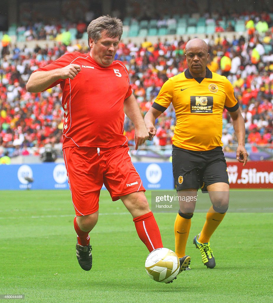 In this handout image provided by the ITM Group, Jan Molby of Liverpool FC Legends and Doctor Khumalo of Kaizer Chiefs Legends (R) during the Legends match between Liverpool FC Legends and Kaizer Chiefs Legends at Moses Mabhida Stadium on November 16, 2013 in Durban, South Africa.