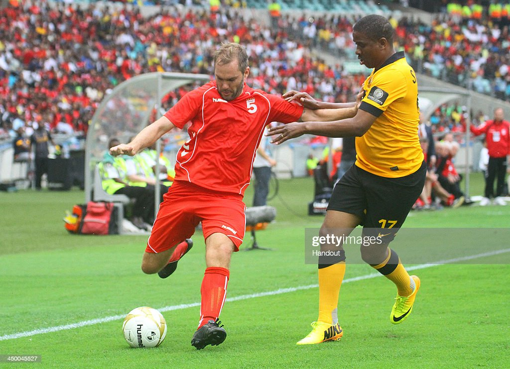 In this handout image provided by the ITM Group, Jason McAteer of Liverpool FC Legends tries to hold off Abel Shongwe of Kaizer Chiefs Legends (R) during the Legends match between Liverpool FC Legends and Kaizer Chiefs Legends at Moses Mabhida Stadium on November 16, 2013 in Durban, South Africa.