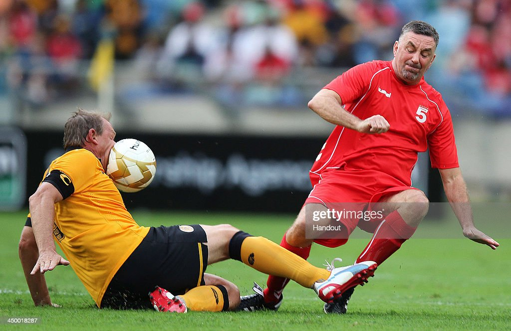 In this handout image provided by the ITM Group, John Aldridge kicks the ball into Neil Tovey during the Legends match between Liverpool FC Legends and Kaizer Chiefs Legends at Moses Mabhida Stadium on November 16, 2013 in Durban, South Africa.