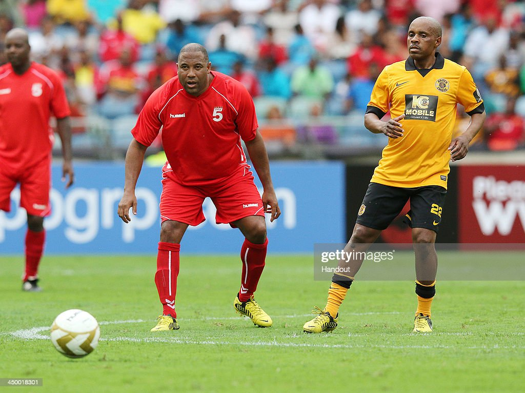 In this handout image provided by the ITM Group, John Barnes passes the ball ahead of Frank Makua during the Legends match between Liverpool FC Legends and Kaizer Chiefs Legends at Moses Mabhida Stadium on November 16, 2013 in Durban, South Africa.