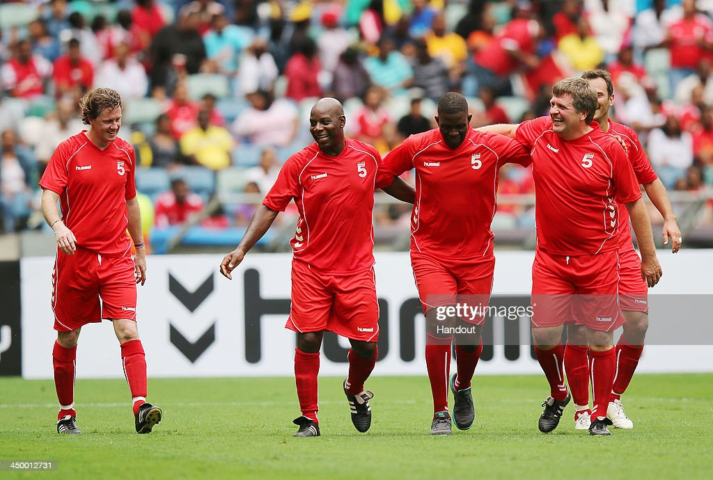 In this handout image provided by the ITM Group, Michael Thomas and Jan Molby celebrate with a competition winner during the Legends match between Liverpool FC Legends and Kaizer Chiefs Legends at Moses Mabhida Stadium on November 16, 2013 in Durban, South Africa.