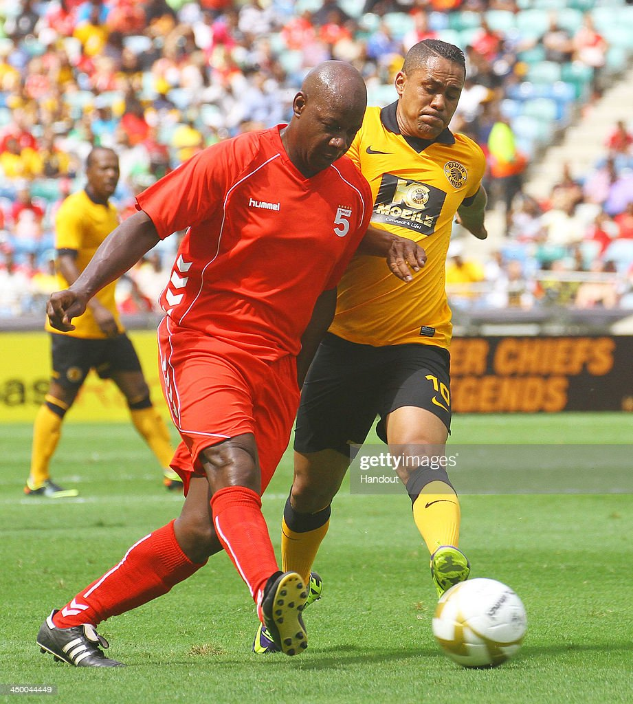 In this handout image provided by the ITM Group, Michael Thomas of Liverpool FC Legends holds off Stanton Fredericks of Kaizer Chiefs during the Legends match between Liverpool FC Legends and Kaizer Chiefs Legends at Moses Mabhida Stadium on November 16, 2013 in Durban, South Africa.