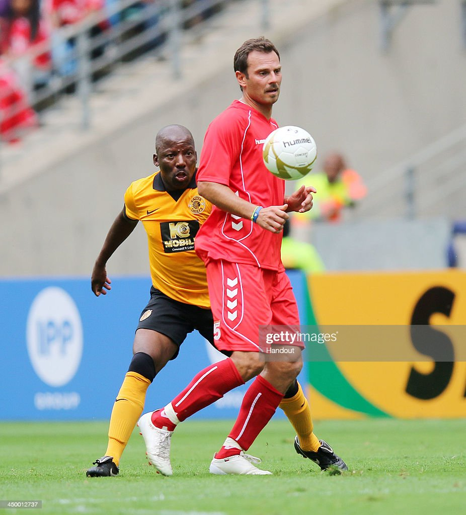 In this handout image provided by the ITM Group, Patrik Berger of Liverpool passes the ball under pressure from Ntsie Maphike during the Legends match between Liverpool FC Legends and Kaizer Chiefs Legends at Moses Mabhida Stadium on November 16, 2013 in Durban, South Africa.