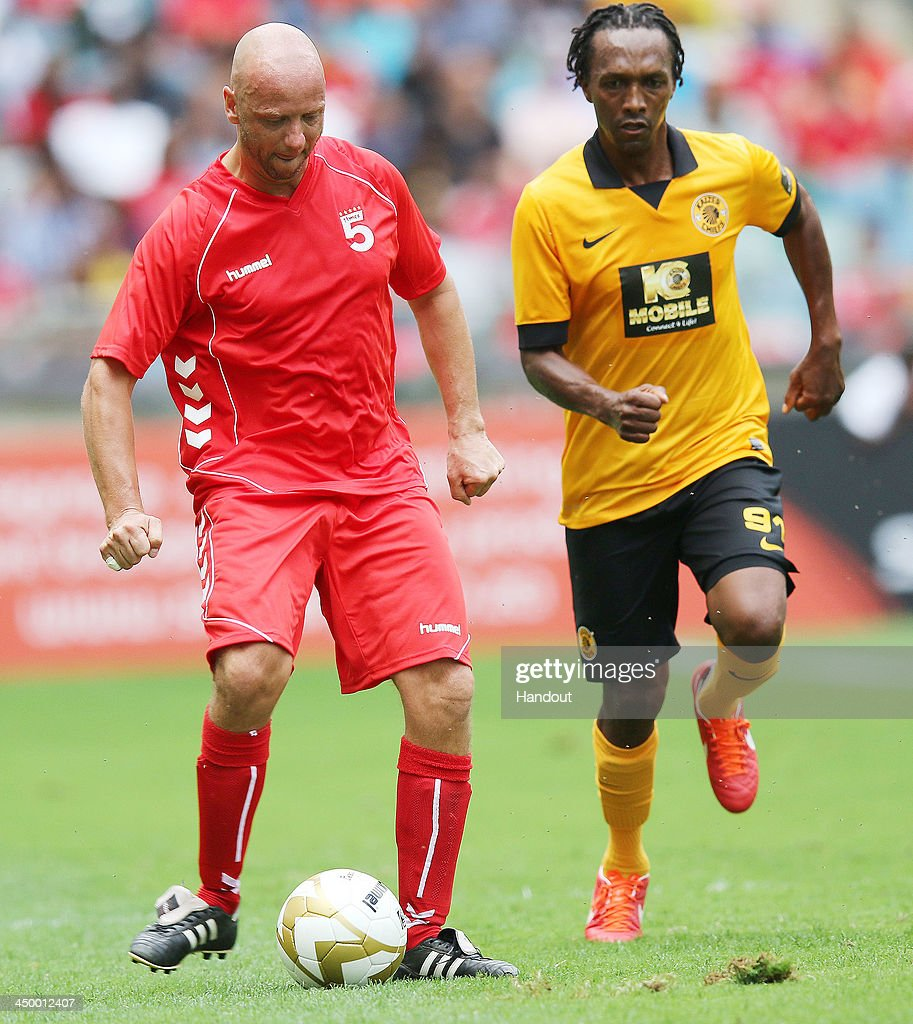 In this handout image provided by the ITM Group, Rob Jones ( L) holds the ball from John Mosheu during the Legends match between Liverpool FC Legends and Kaizer Chiefs Legends at Moses Mabhida Stadium on November 16, 2013 in Durban, South Africa.