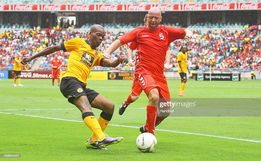 In this handout image provided by the ITM Group, Rob Jones of Liverpool FC Legends tries to stop Arthur Zwane Kaizer Chiefs Legends from crossing the ball during the Legends match between Liverpool FC Legends and Kaizer Chiefs Legends at Moses Mabhida Stadium on November 16, 2013 in Durban, South Africa.
