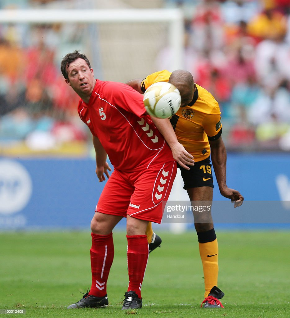 In this handout image provided by the ITM Group, Robbie Fowler and Lucas Radebe (R) battle for the ball during the Legends match between Liverpool FC Legends and Kaizer Chiefs Legends at Moses Mabhida Stadium on November 16, 2013 in Durban, South Africa.