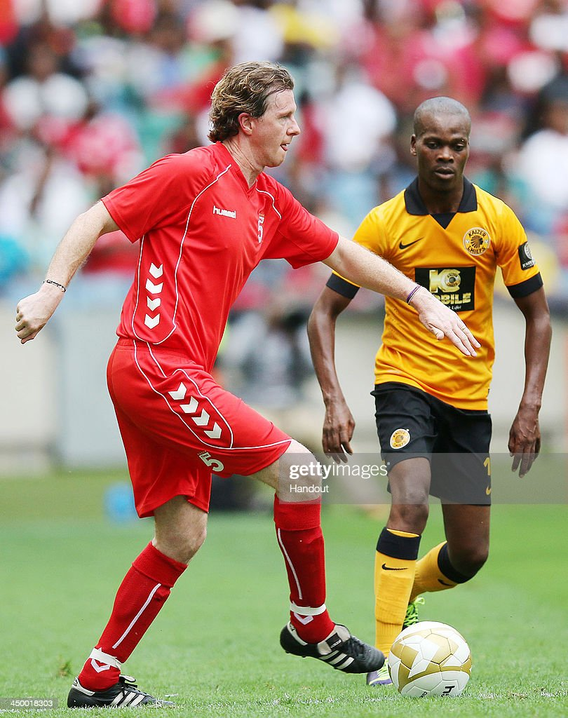 In this handout image provided by the ITM Group, Steve McManaman beats Arthur Zwane to the ball during the Legends match between Liverpool FC Legends and Kaizer Chiefs Legends at Moses Mabhida Stadium on November 16, 2013 in Durban, South Africa.