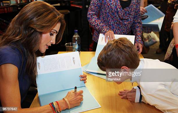 In this handout image provided by the Jordan Royal Household Queen Rania of Jordan signs a copy of 'The Sandwich Swap' in the United Nations Bookshop...