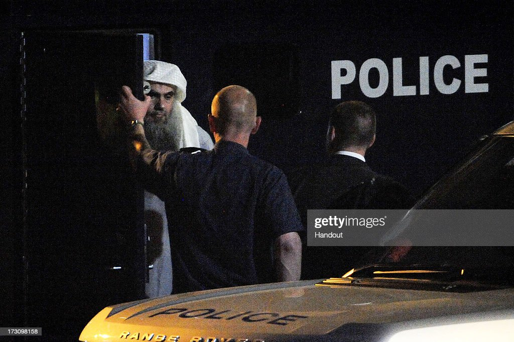 In this handout image provided by the MoD, radical cleric Abu Qatada (L) prepares to board a plane at RAF Northolt which will take him to Jordan, after he was deported from the UK to face terrorism charges in his home country, on July 7, 2013 in London, England.