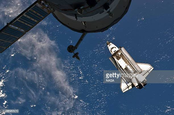 In this handout image provided by the National Aeronautics and Space Administration NASA space shuttle Atlantis in Earth orbit just before docking...