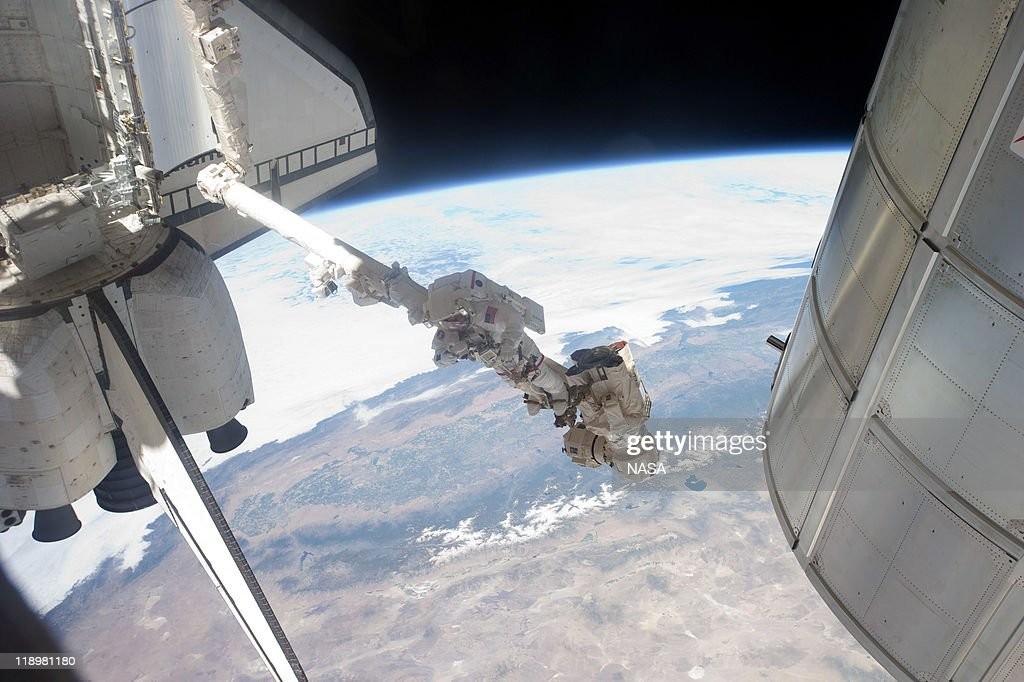 In this handout image provided by the National Aeronautics and Space Administration (NASA), NASA astronaut Mike Fossum attached to the robotic arm Canadarm2 takes a picture during a planned six-and-a-half-hour spacewalk July 12, 2011 in space. This is the 160th spacewalk devoted to station assembly and maintenance since construction began in 1998. Space shuttle Atlantis has embarked on a 12-day mission to the International Space Station where it will deliver the Raffaello multi-purpose logistics module packed with supplies and spare parts. This will be the final launch of the space shuttle program, which began on April 12, 1981 with the launch of Colombia.