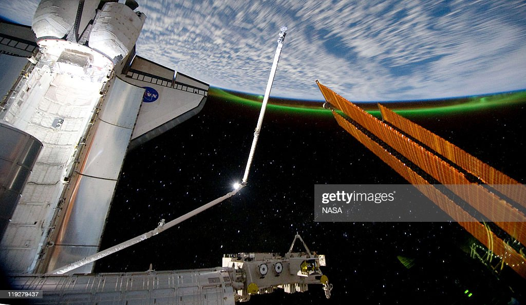 In this handout image provided by the National Aeronautics and Space Administration (NASA), the Southern Lights or Aurora Australis ring planet earth as the docked space shuttle Atlantis' cargo bay (L) and the solar array panel of the International Space Station are seen July 14, 2011 in space. Space shuttle Atlantis is on the last leg of a 12-day mission to the International Space Station where it delivered the Raffaello multi-purpose logistics module packed with supplies and spare parts. This was the final mission of the space shuttle program, which began on April 12, 1981 with the launch of Colombia.