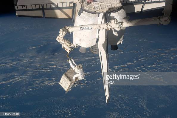 In this handout image provided by the National Aeronautics and Space Administration NASA astronaut Ronald Garan attached to the robotic arm Canadarm2...