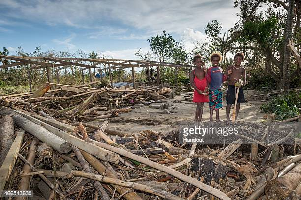 In this handout image provided by the New Zealand Defence Force children stand around the remains of a local community centre destroyed in the...