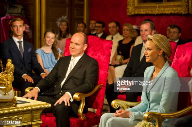 In this handout image provided by the Palais Princier Prince Albert II of Monaco and Princess Charlene of Monaco are seated in the Throne Room during...