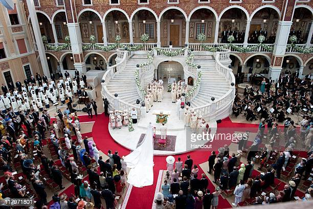 In this handout image provided by the Palais Princier Princess Charlene of Monaco and Prince Albert II of Monaco stand during the religious ceremony...
