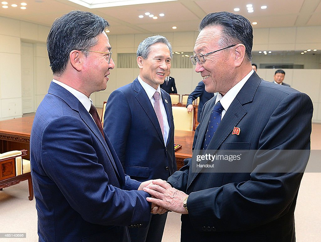 In this handout image provided by the South Korean Unification Ministry, South Korean Unification Minister Hong Yong-Pyo (L) shakes hands with <a gi-track='captionPersonalityLinkClicked' href=/galleries/search?phrase=Kim+Yang-Gon&family=editorial&specificpeople=4679241 ng-click='$event.stopPropagation()'>Kim Yang-Gon</a> (R) a senior North Korean official responsible for South Korean affairs, as South Korean presidential security adviser <a gi-track='captionPersonalityLinkClicked' href=/galleries/search?phrase=Kim+Kwan-Jin&family=editorial&specificpeople=4112030 ng-click='$event.stopPropagation()'>Kim Kwan-Jin</a> looks on after their meeting at the Panmunjom on August 25, 2015 in Paju, South Korea. Both countries came to an agreement to ease tensions after an exchange of artillery fire last week.