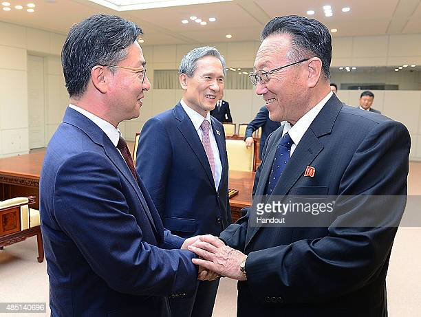 In this handout image provided by the South Korean Unification Ministry South Korean Unification Minister Hong YongPyo shakes hands with Kim YangGon...
