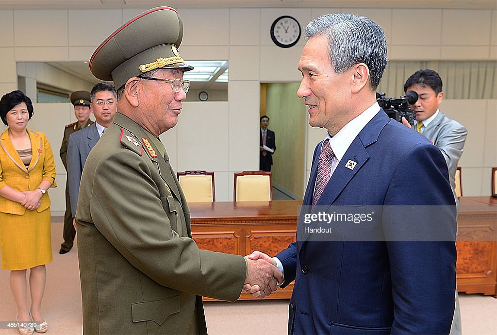 In this handout image provided by the South Korean Unification Ministry, South Korean presidential security adviser <a gi-track='captionPersonalityLinkClicked' href=/galleries/search?phrase=Kim+Kwan-Jin&family=editorial&specificpeople=4112030 ng-click='$event.stopPropagation()'>Kim Kwan-Jin</a> (R) shakes hands with <a gi-track='captionPersonalityLinkClicked' href=/galleries/search?phrase=Hwang+Pyong-So&family=editorial&specificpeople=13629767 ng-click='$event.stopPropagation()'>Hwang Pyong-So</a> (L) North Korea' top political officer for the Korean People's Army after their meeting at the Panmunjom on August 25, 2015 in Paju, South Korea. Both countries came to an agreement to ease tensions after an exchange of artillery fire last week.