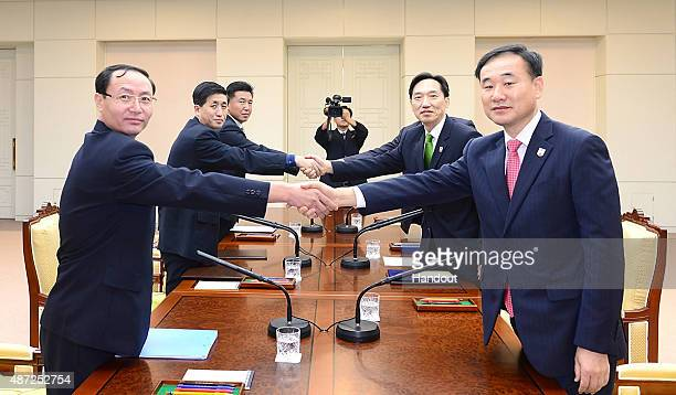 In this handout image provided by the South Korean Unification Ministry South Korean chief delegate Lee DeokHaeng shake hands with his North Korean...