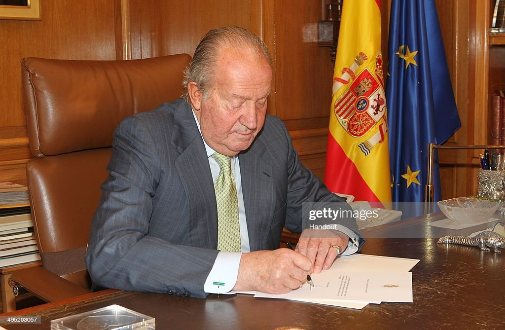 In this handout image provided by the Spanish Royal Palace King Juan Carlos of Spain signs papers to confirm his abdication on June 02 2014 in Madrid...