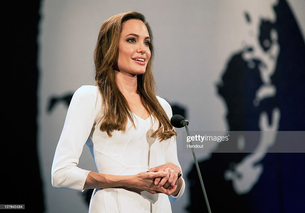 In this handout image provided by the UNHCR, Goodwill Ambassador <a gi-track='captionPersonalityLinkClicked' href=/galleries/search?phrase=Angelina+Jolie&family=editorial&specificpeople=201591 ng-click='$event.stopPropagation()'>Angelina Jolie</a> presents the 2011 Nansen Refugee Award at a ceremony on October 3, 2011 in Geneva, Switzerland. The prize was awarded to the founder and 290 staff of SHS, a non-governmental organization, for their life-saving work in helping the thousands of refugees and migrants who arrive on Yemen's shores each year.