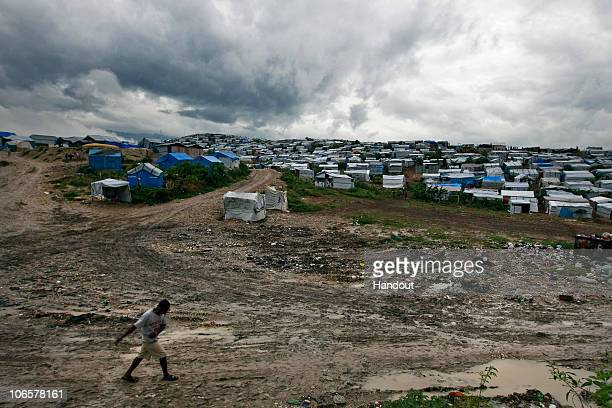 In this handout image provided by the United Nations Stabilization Mission in Haiti a man walks through mud at a camp for displaced people of the...
