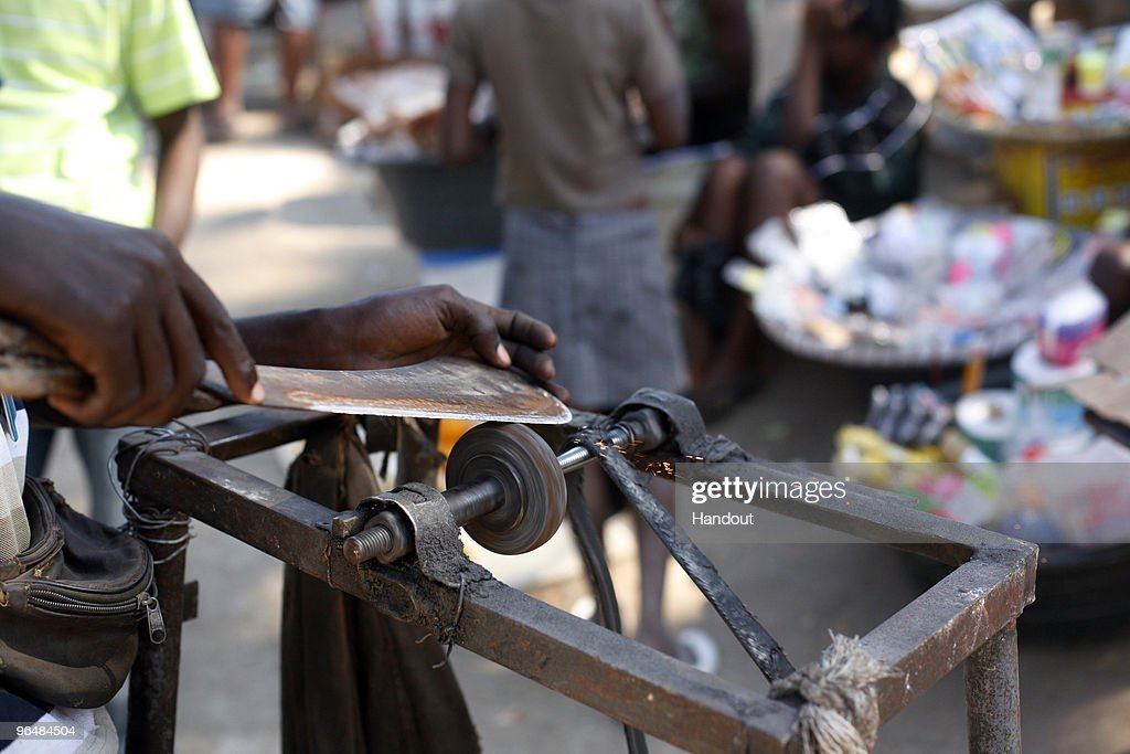 In this handout image provided by the United Nations Stabilization Mission in Haiti A man sharpens a machete in the Petionville Club IDP camp where...
