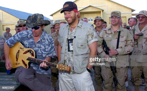 In this handout image provided by the United Service Organizations country music star Toby Keith and rock guitarist and noted outdoorsman Ted Nugent...