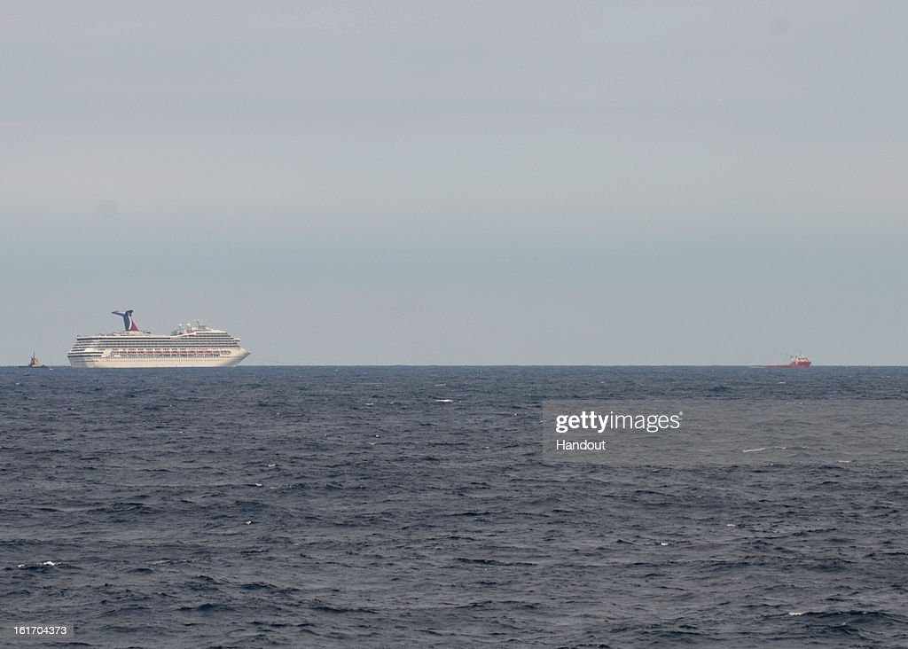 In this handout image provided by the US Coast Guard, The Carnival Cruise Ship Triumph is towed by the tugboats Pioneer and Roland Falgout toward Mobile, Alabama February 13, 2013 in the Gulf of Mexico. The cruise ship is expected to arrive in Mobile Thursday night.