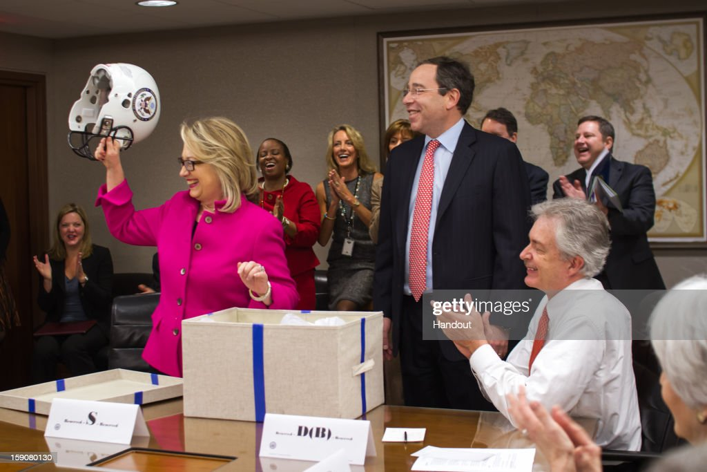 In this handout image provided by the U.S. Department of State, Secretary of State Hillary Clinton receives a football helmet from Deputy Secretary Tom Nides (C) during a State Department meeting January 7, 2013 in Washington, DC. Clinton returned to work today after recovering from a fall where she hit her head and doctors later detected a blood clot.