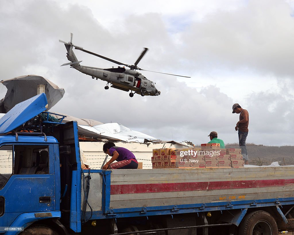 In this handout image provided by the U.S. Navy, a Sea Hawk from Saberhawks of Helicopter Maritime Strike Squadron 77 departs Guiuan airstrip to conduct an airlift mission in support of Operation Damayan while Filipino civilian volunteers load aid supplies onto a truck November 20, 2013 in Guiuan, Philippines. The George Washington Carrier Strike Group in coordination with Joint Task Force 505 personnel is assisting the Philippine Government in ongoing relief efforts in response to the aftermath of Super Typhoon Haiyan.