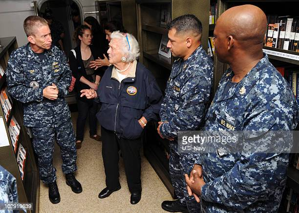 In this handout image provided by the US Navy Command Chaplain Cmdr Cameron Fish and former first lady Barbara Bush tour the library of the aircraft...
