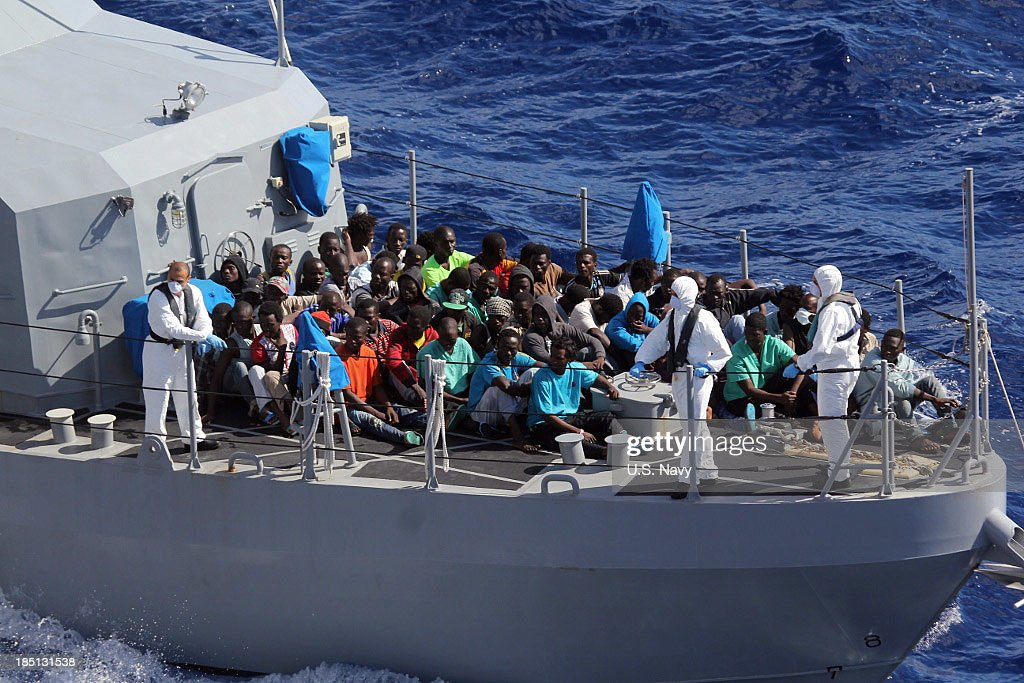 In this handout image provided by the U.S. Navy, distressed persons sit on the deck of an Armed Forces of Malta offshore patrol vessel after being transferred from the amphibious transport dock ship USS San Antonio October 17, 2013 in the Mediterranean Sea. San Antonio provided food, water, medical attention, and temporary shelter to the 128 men who were rescued October 16 from an inflatable raft that was adrift after responding to a call by the Maltese Government.