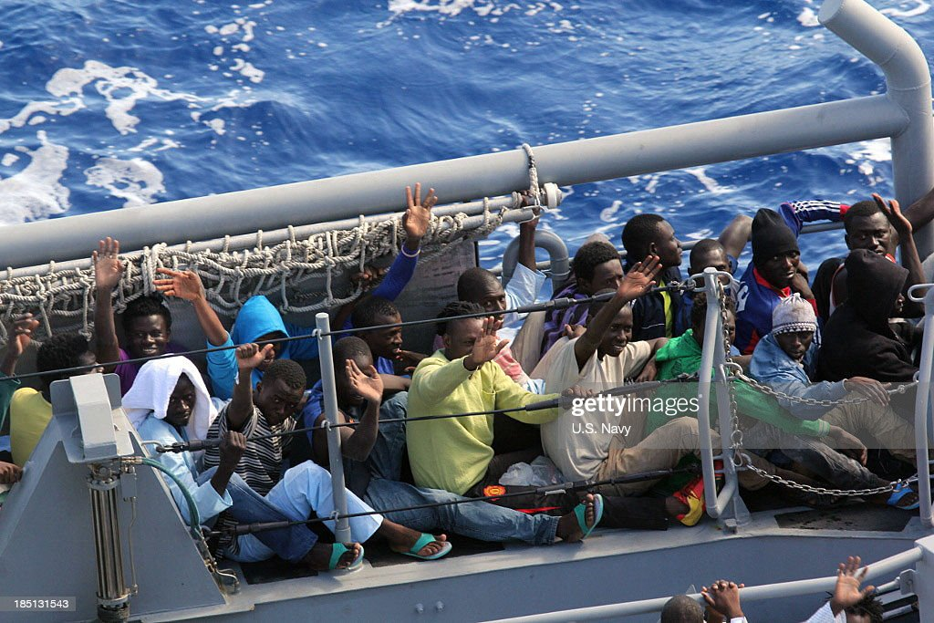 In this handout image provided by the U.S. Navy, distressed persons wave after being transferred from the amphibious transport dock ship USS San Antonio to an Armed Forces of Malta offshore patrol vessel October 17, 2013 in the Mediterranean Sea. San Antonio provided food, water, medical attention, and temporary shelter to the 128 men who were rescued October 16 from an inflatable raft that was adrift after responding to a call by the Maltese Government.