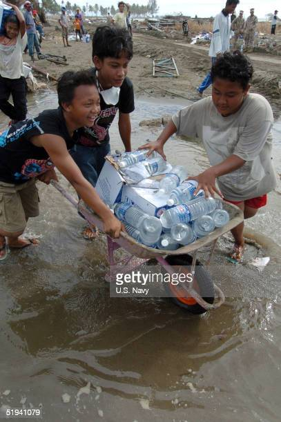 MEULABOH SUMATRA INDONESIA JANUARY 11 In this handout image provided by the US Navy Indonesian children carry bottles of drinking water in a...