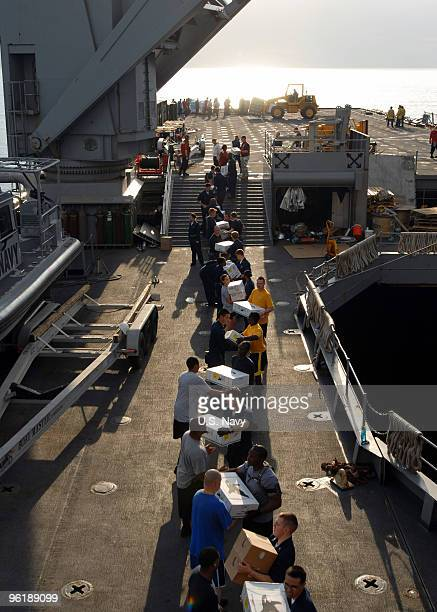 In this handout image provided by the US Navy Sailors and Marines onload stores and relief supplies aboard the amphibious dock landing ship USS Fort...