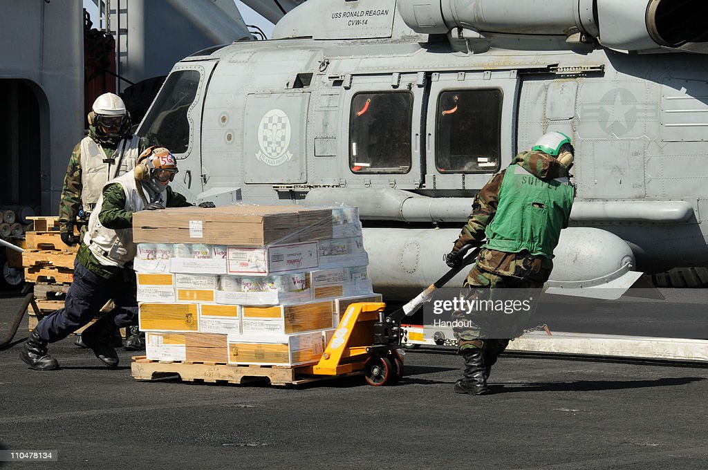 In this handout image provided by the US Navy sailors move food and humanitarian assistance supplies across the flight deck of the aircraft carrier...