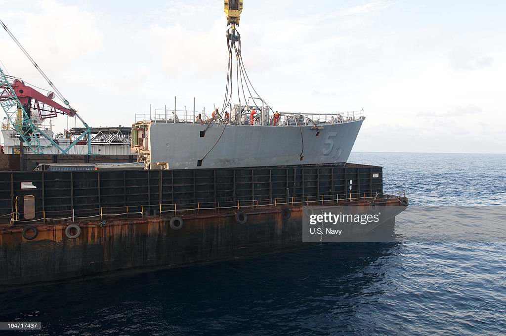 In this handout image provided by the U.S. Navy, the U.S. Navy contracted crane vessel M/V Jascon 25 removes the bow of the mine countermeasure ship ex-Guardian (MCM 5) on March 26, 2013 in Sulu Sea, Philippines. The U.S. Navy and contracted salvage teams continue damage assessments and the removal of equipment and parts to prepare the grounded ship to be safely dismantled. The U.S. Navy continues to work in close cooperation with the Philippine authorities to safely dismantle Guardian from the reef while minimizing environmental effects. Guardian ran aground on the Tubbataha Reef January 17.